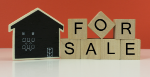 Orange background with chalkboard house and for sale building cubes